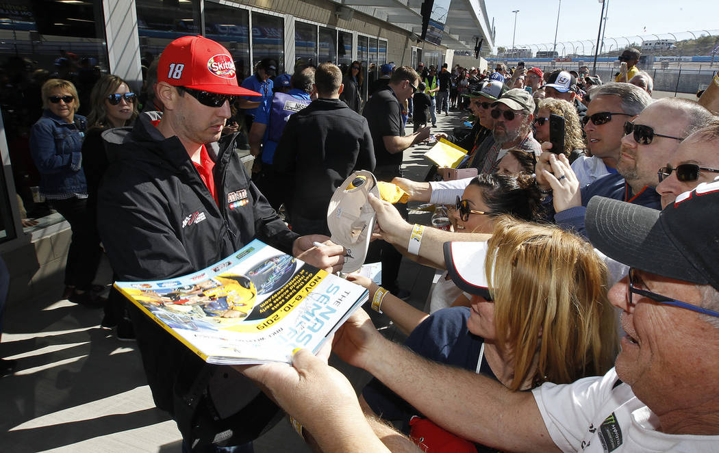 Kyle Busch (18) signs autographs for fans outside the drivers meeting room prior to the start of the NASCAR Cup Series auto race at ISM Raceway, Sunday, March 10, 2019, in Avondale, Ariz. (AP Phot ...