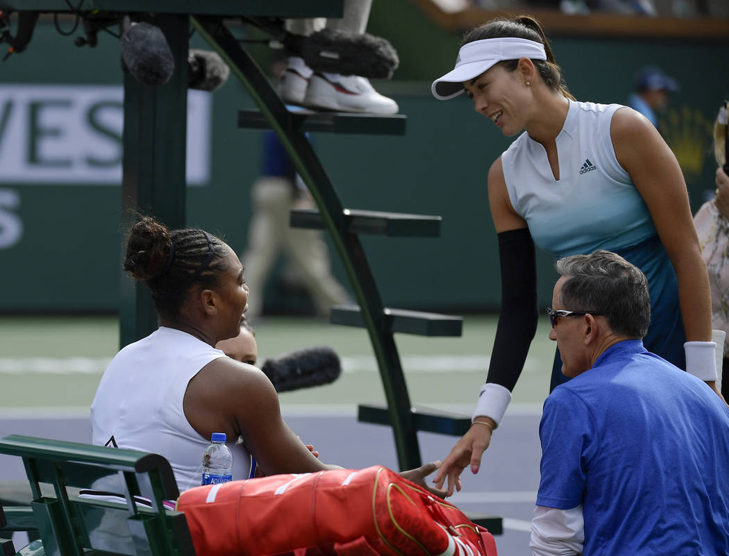Garbine Muguruza, of Spain, right, speaks with Serena Williams, left, during their match at the BNP Paribas Open tennis tournament Sunday, March 10, 2019, in Indian Wells, Calif. Williams retired ...
