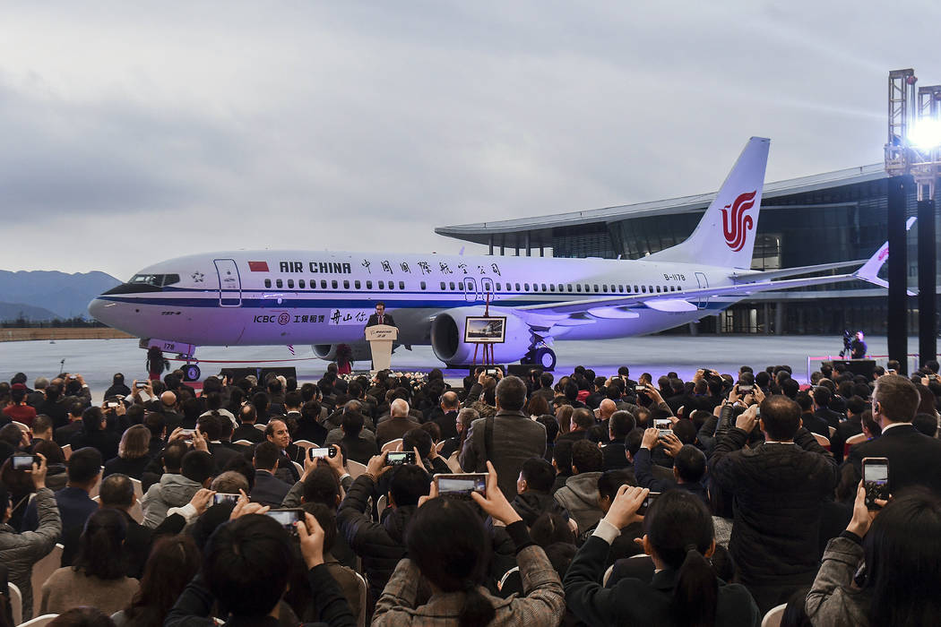 Invited guests take photos of the Boeing 737 Max 8 airplane deliver to Air China during a ceremony at Boeing Zhoushan 737 Completion and Delivery Center in Zhoushan, east China's Zhejiang Province ...