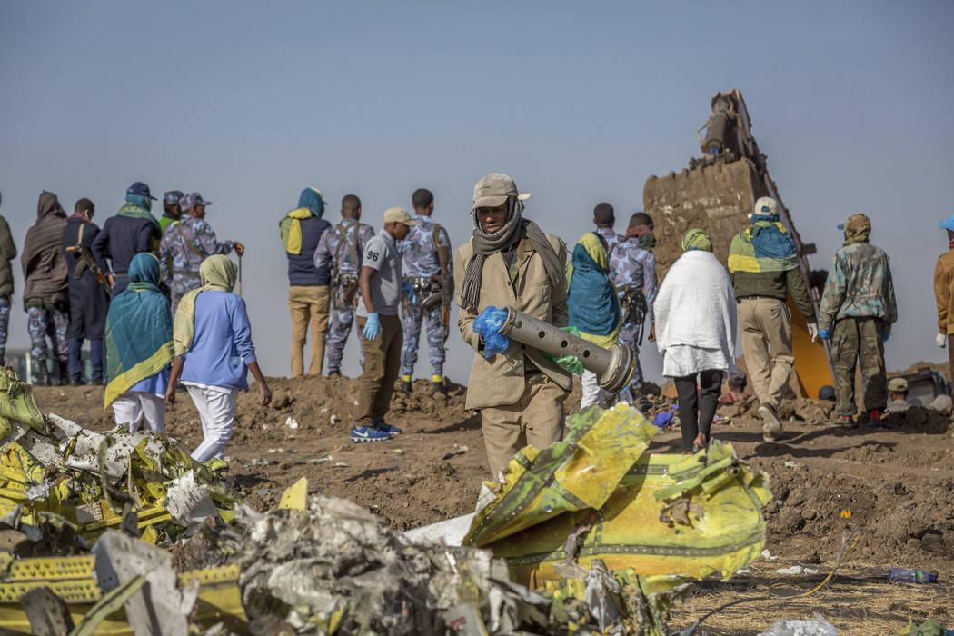 Workers gather at the scene of an Ethiopian Airlines flight crash near Bishoftu, or Debre Zeit, south of Addis Ababa, Ethiopia, Monday, March 11, 2019. A spokesman says Ethiopian Airlines has gro ...