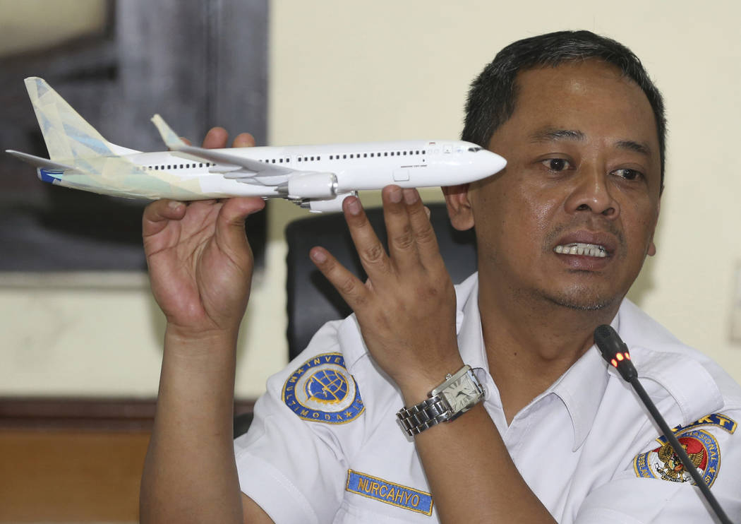 National Transportation Safety Committee investigator Nurcahyo Utomo holds a model of an airplane during a press conference on the committee's preliminary findings on their investigation on the cr ...