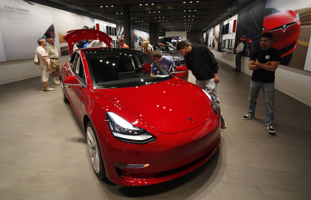 Prospective customers confer with sales associates as a Model 3 sits on display in a Tesla showroom in the Cherry Creek Mall in Denver. (AP Photo/David Zalubowski, File)