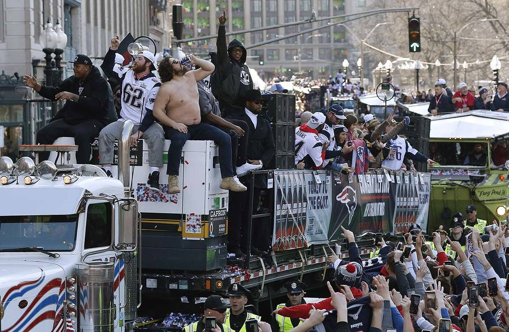 New England Patriots' Trent Brown, left, and Joe Thuney, center, sit beside David Andrews as he chugs a beverage during the team's parade through downtown Boston, Tuesday, Feb. 5, 2019, to celebra ...