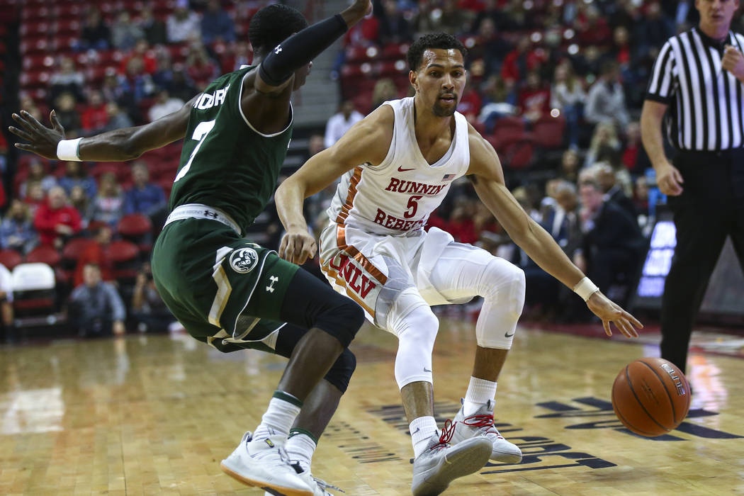 UNLV Rebels guard Noah Robotham (5) brings the ball up court against Colorado State guard Kendle Moore during the first half of a basketball game at the Thomas & Mack Center in Las Vegas on We ...