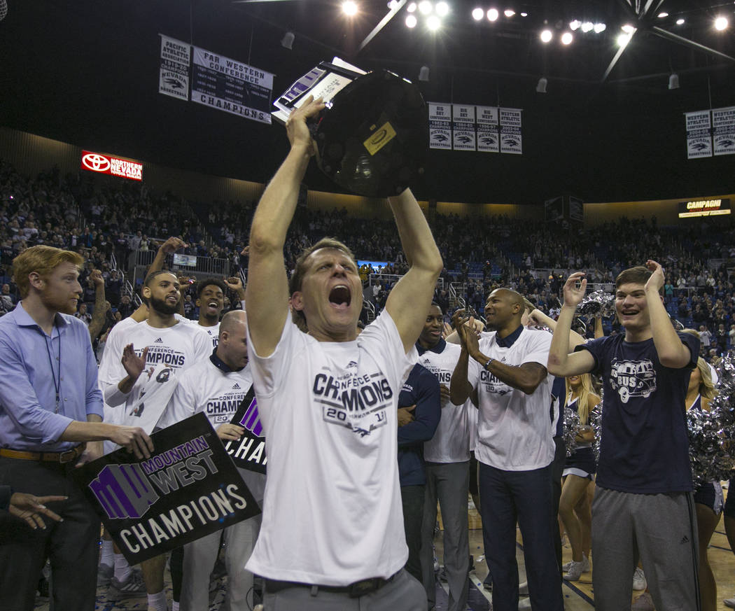 Nevada head coach Eric Musselman holds up the Mountain West Championship trophy after his team's win over San Diego State in an NCAA college basketball game in Reno, Nev., Saturday, March 9, 2019. ...