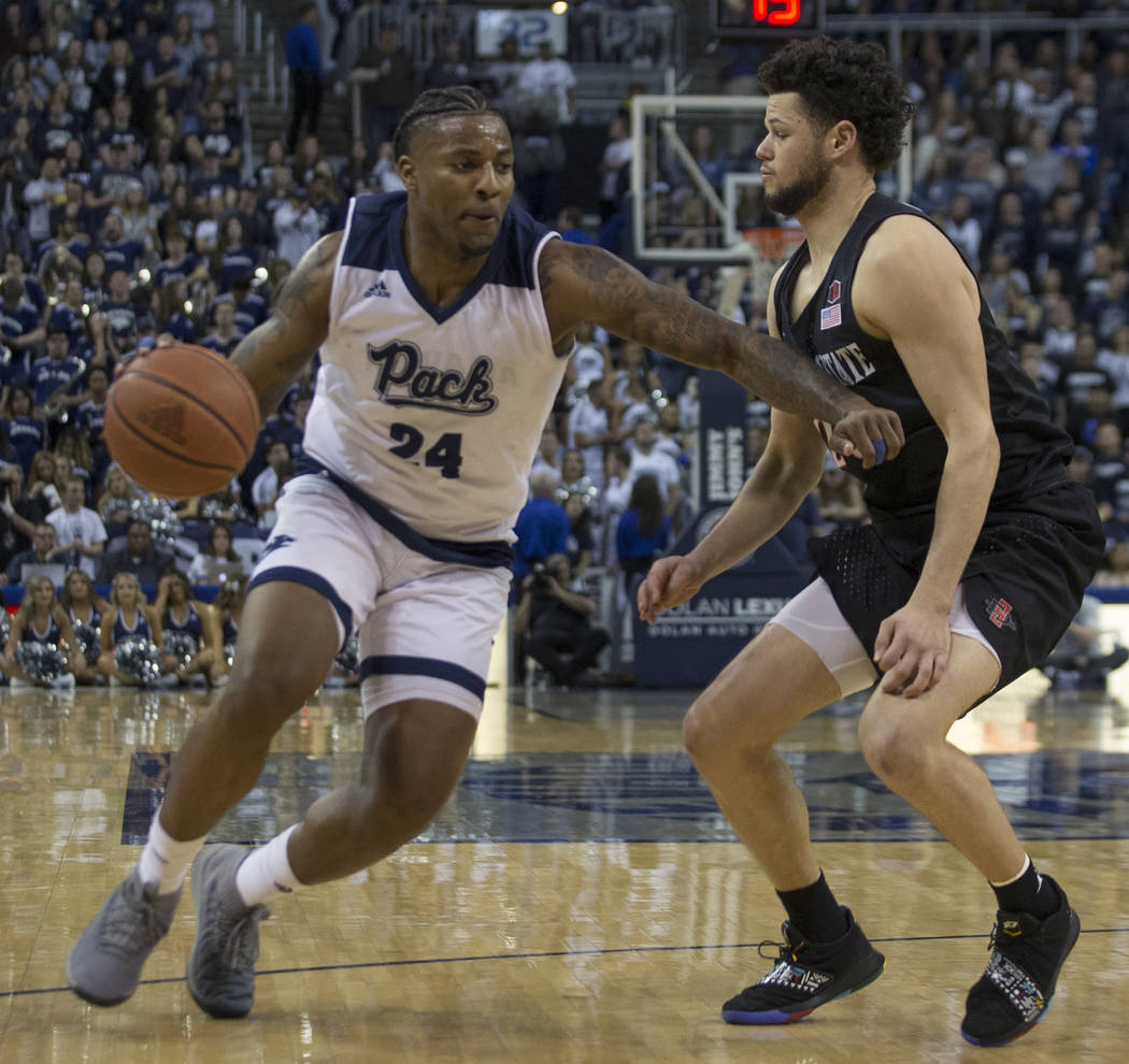 Nevada forward Jordan Caroline (24) drives past San Diego State guard Jordan Schakel (20) in the second half of an NCAA college basketball game in Reno, Nev., Saturday, March 9, 2019. (AP Photo/To ...