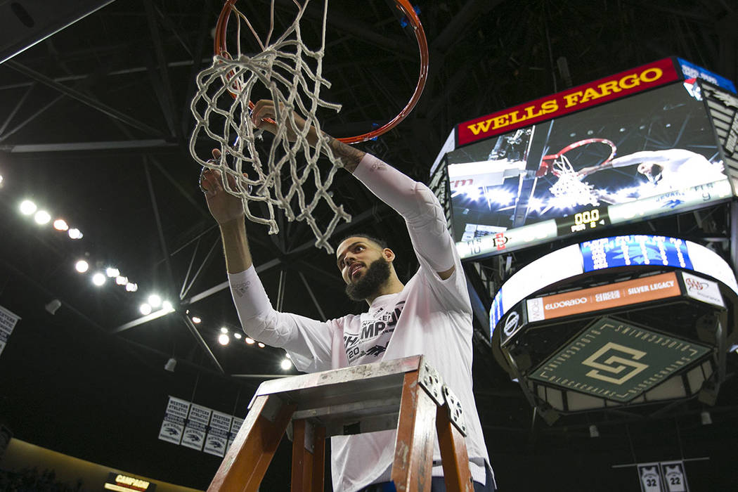 Nevada forward Cody Martin (11) cuts down the net after his teams win over San Diego State in an NCAA college basketball game in Reno, Nev., Saturday, March 9, 2019. (AP Photo/Tom R. Smedes)