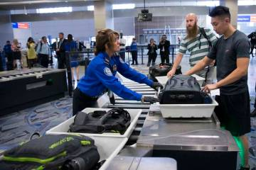 Transportation Security Administration agent Donna Franco, left, assists a passenger in one of the new automated screening lanes at McCarran International Airport Terminal 1 in Las Vegas, Aug. 31, ...