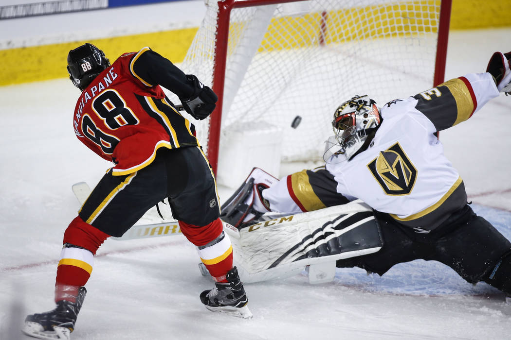 Vegas Golden Knights goalie Malcolm Subban, right, lets in a goal from Calgary Flames' Andrew Mangiapane during first period NHL hockey action in Calgary, Alberta, Sunday, March 10, 2019. (Jeff Mc ...