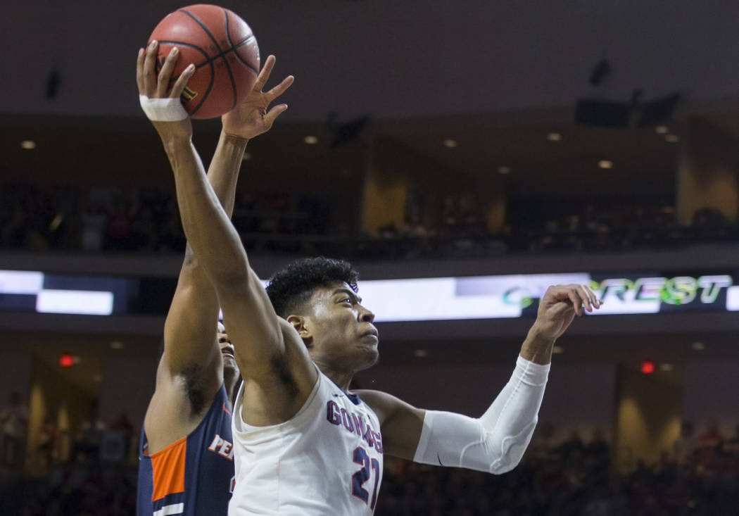 Gonzaga junior forward Rui Hachimura (21) drives past Pepperdine senior guard Eric Cooper Jr. (21) in the first half during the West Coast Conference semifinal game on Monday, March 11, 2019, at O ...