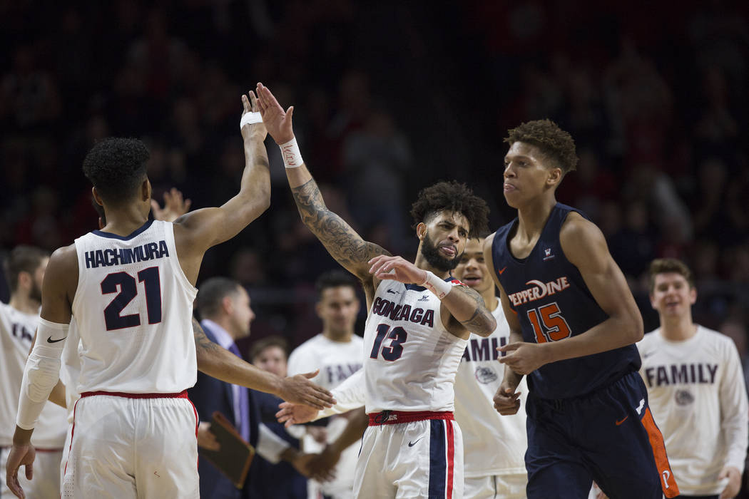 Gonzaga senior guard Josh Perkins (13) celebrates with junior forward Rui Hachimura (21) in the second half during their West Coast Conference semifinal game with Pepperdine on Monday, March 11, 2 ...