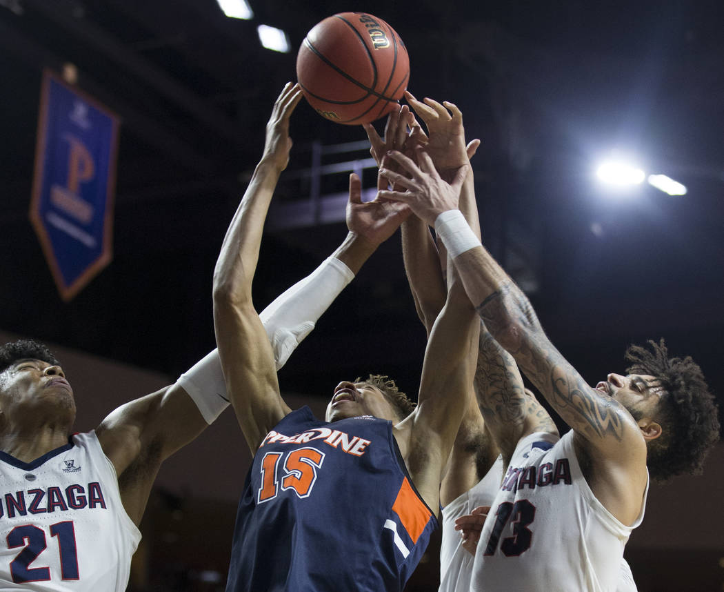 Gonzaga junior forward Rui Hachimura (21) and senior guard Josh Perkins (13) fight for a loose ball with Pepperdine freshman forward Kessler Edwards (15) in the second half during the West Coast C ...