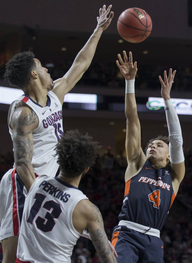 Pepperdine sophomore guard Colbey Ross (4) shoots a jump shot over Gonzaga junior forward Brandon Clarke (15) and senior guard Josh Perkins (13) in the second half during the West Coast Conference ...