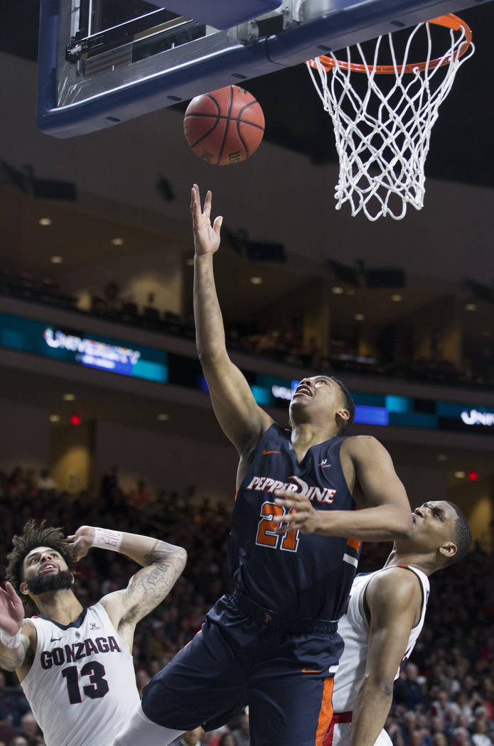 Pepperdine senior guard Eric Cooper Jr. (21) slices to the rim past Gonzaga senior guard Josh Perkins (13) in the second half during the West Coast Conference semifinal game on Monday, March 11, 2 ...