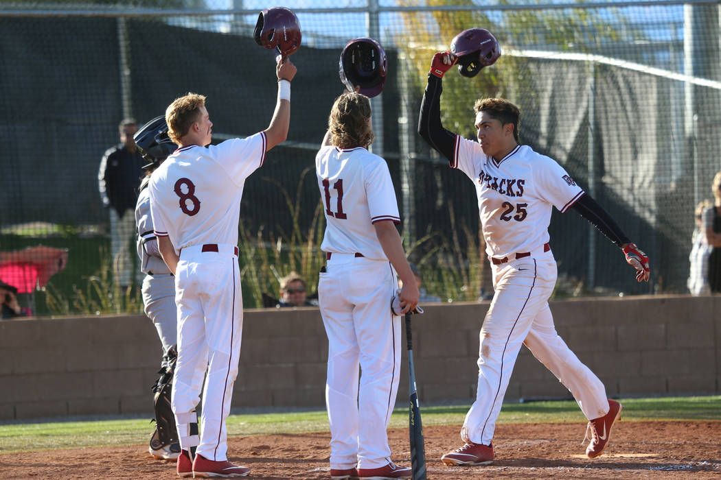 Desert Oasis' Aaron Roberts (25) scores a run with a homerun and celebrates with teammates Josh Sharman (11) and Zac Czerniawski (8) in the baseball game against Palo Verde at Desert Oasis High Sc ...