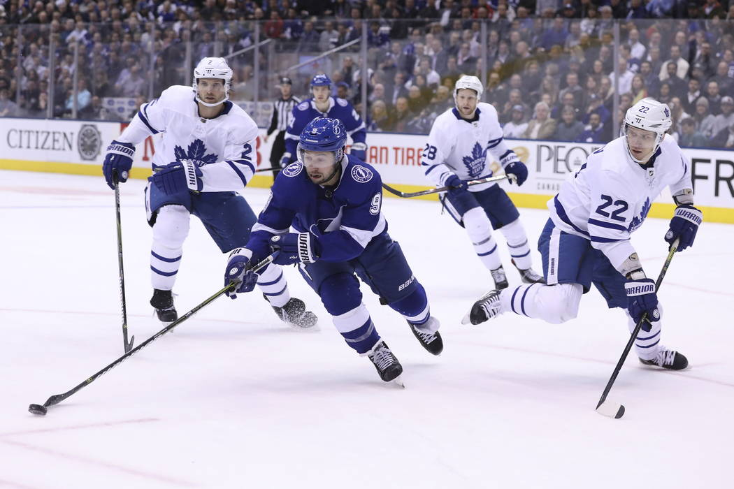 Tampa Bay Lightning center Tyler Johnson (9) controls the puck by Toronto Maple Leafs defensemen Nikita Zaitsev (22) and Ron Hainsey (2) during second-period NHL hockey game action in Toronto, Mon ...