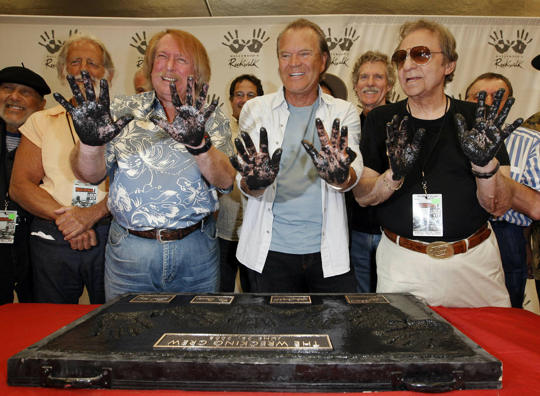 In this June 25, 2008, file photo, Don Randi, from left, Glen Campbell and Hal Blaine, representing session musicians known as The Wrecking Crew, hold up their hands after placing them in the ceme ...