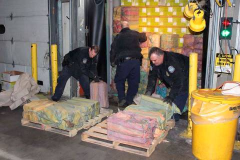 This Feb. 28, 2019 photo provided by U. S. Customs and Border Protection shows Customs agents unloading a truck containing 3,200 pounds of cocaine in 60 packages, where it was seized at the Port o ...