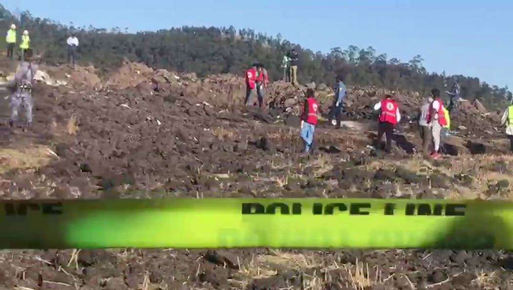 In this image taken from video, rescuers search through wreckage at the scene of an Ethiopian Airlines flight that crashed shortly after takeoff at Hejere near Bishoftu, or Debre Zeit, some 50 kil ...
