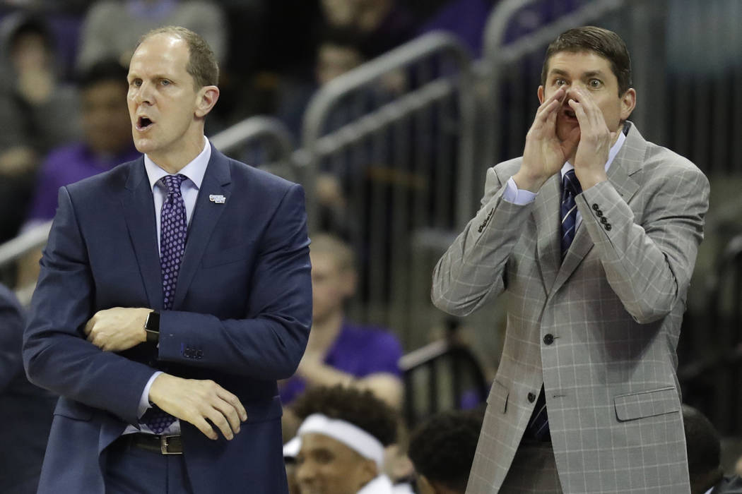 In this Sunday, Jan. 28, 2018 photo, Washington head coach Mike Hopkins, left, calls to his team along with assistant coach Dave Rice, right,, during the first half of an NCAA college basketball g ...