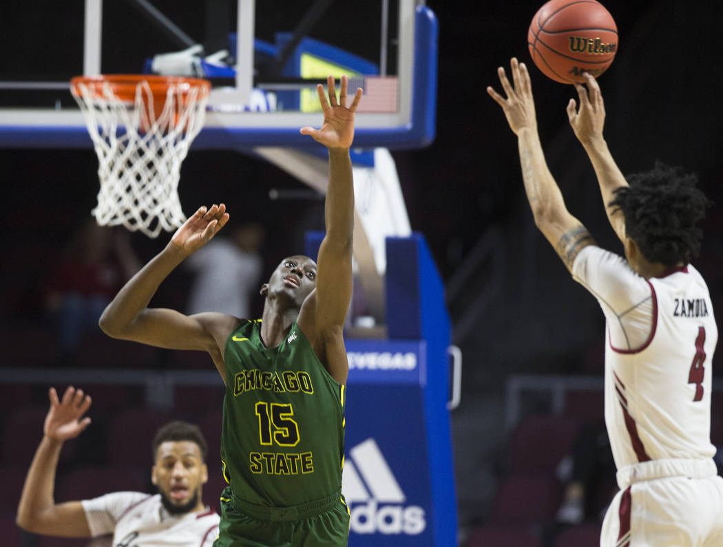 Chicago State sophomore center Noah Bigirumwami (15) reaches to block the shot of New Mexico State senior guard JoJo Zamora (4) in the second half of the opening round of the Western Athletic Conf ...