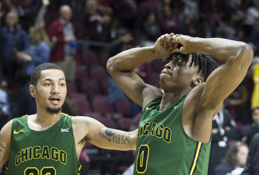 Chicago State senior forward Ken Odiase (0) is comforted by teammate Michael Johnson (22) after the Cougars lost to New Mexico State 86-49 in the opening round of the Western Athletic Conference t ...