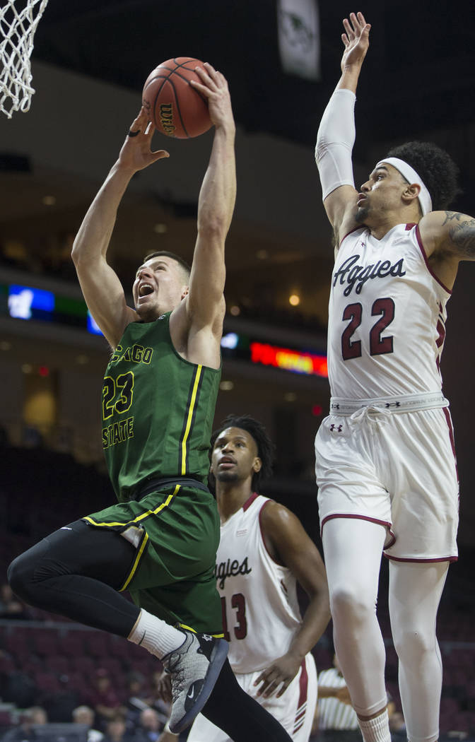 Chicago State junior forward Patrick Szpir (23) drives to the rim past New Mexico State senior forward Eli Chuha (22) in the first half of the opening round of the Western Athletic Conference tour ...