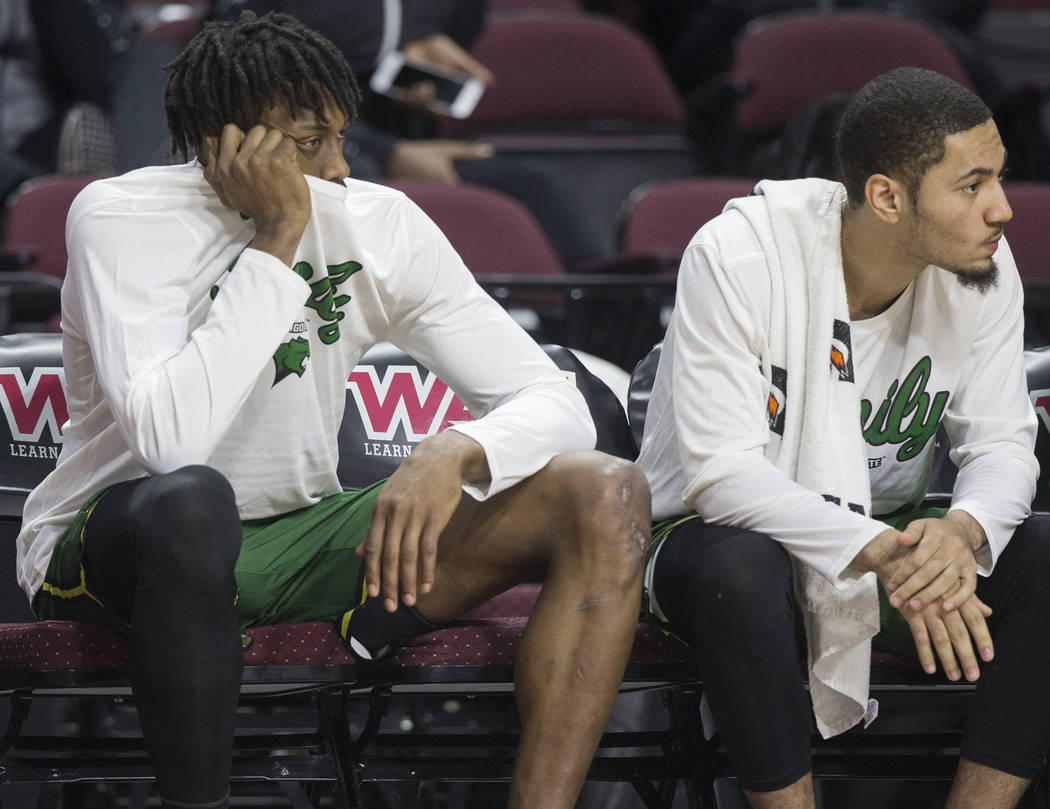 Chicago State senior forward Ken Odiase, left, sits dejected on the bench as time winds down on a 86-49 loss to New Mexico State in the opening round of the Western Athletic Conference tournament ...