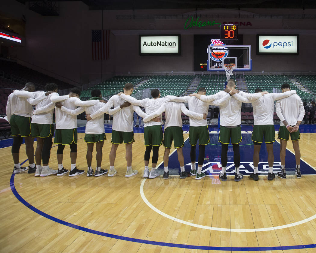 Chicago State locks arms as the national anthem plays before the start of the Cougars opening round Western Athletic Conference tournament game with New Mexico State on Thursday, March 14, 2019, a ...