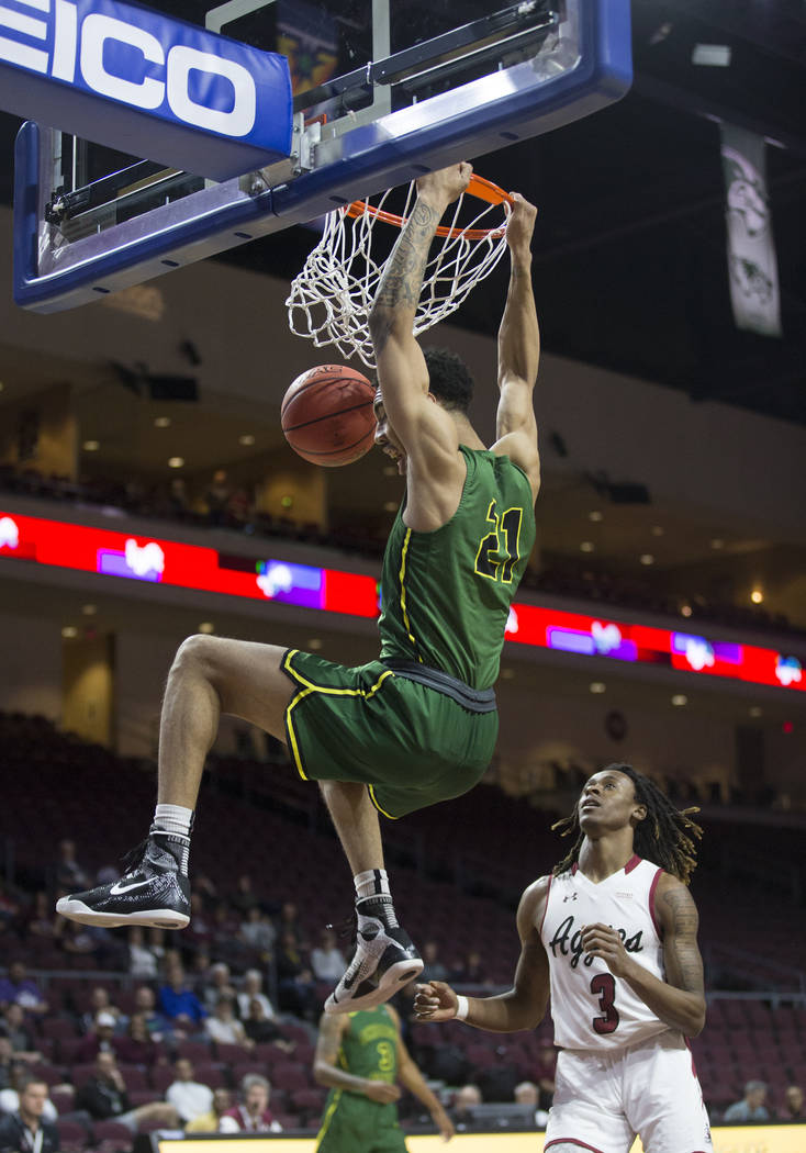 Chicago State sophomore forward Cameron Bowles (21) dunks over New Mexico State junior guard Terrell Brown (3) in the first half of the opening round of the Western Athletic Conference tournament ...