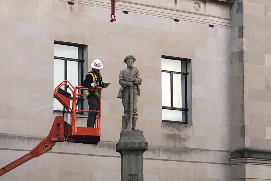 A workman prepares a Confederate staute for removal, Tuesday, March 12, 2019, in Winston-Salem, N.C. Crews began removing the Confederate statue Sunday from the grounds of an old courthouse. North ...