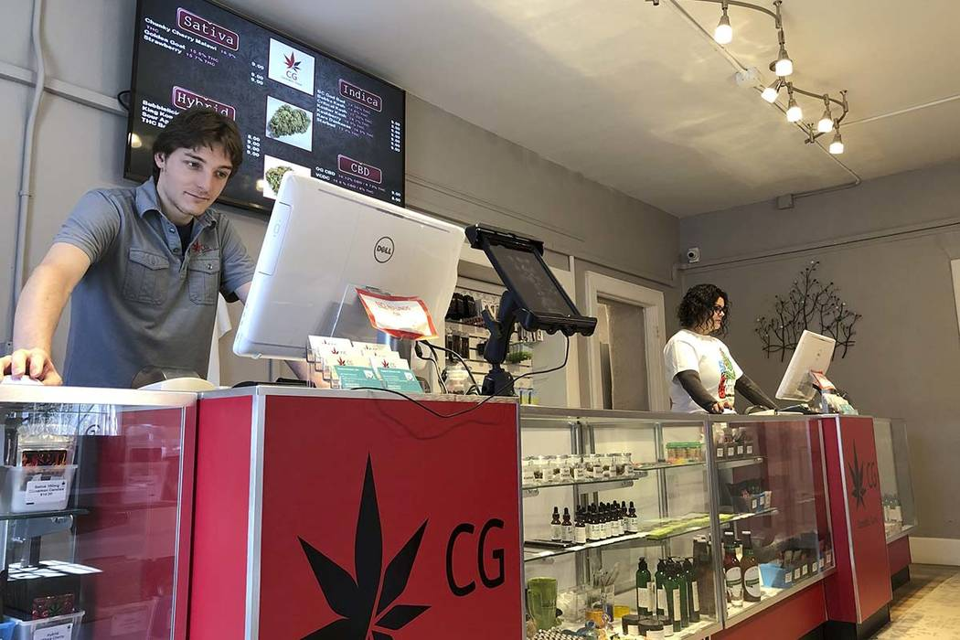 In this Wednesday, March 6, 2019 photo, Korbin Osborn, left, works as a cannabis adviser at a medical marijuana dispensary in Santa Fe, New Mexico. (AP Photo/Morgan Lee)