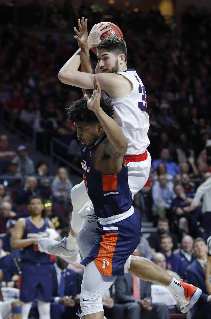 Pepperdine's Darnell Dunn, bottom, fouls Gonzaga's Killian Tillie, top, during the second half of an NCAA semifinal college basketball game at the West Coast Conference tournament, Monday, March 1 ...