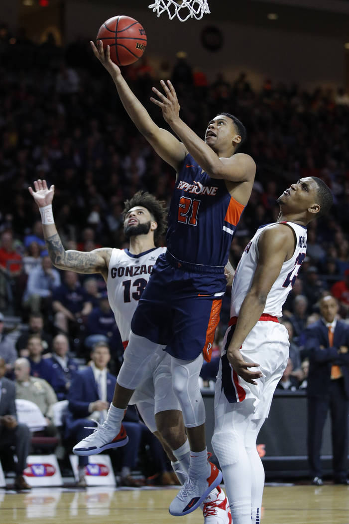 Pepperdine's Eric Cooper Jr. (21) shoots around Gonzaga's Zach Norvell Jr., right, and Josh Perkins during the second half of an NCAA semifinal college basketball game at the West Coast Conference ...