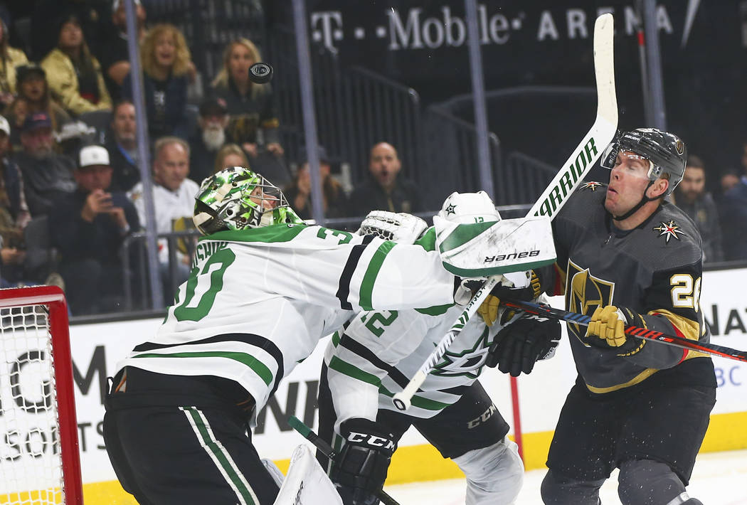 Dallas Stars goaltender Ben Bishop (30) watches the puck while Golden Knights center Paul Stastny, right, gets hit in the face with a stick during the first period of an NHL hockey game at T-Mobil ...