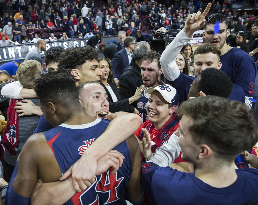 St. Mary's junior guard Jordan Ford, left/top, gets a big hug from sophomore forward Malik Fitts (24) after the Gaels upset Gonzaga 60-47 to win the West Coast Conference championship on Tuesday, ...
