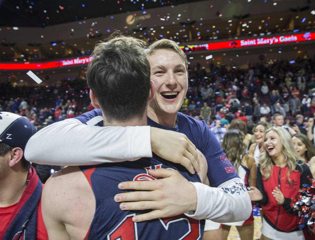 St. Mary's freshman guard Alex Mudronja gets a big hug from teammate Tommy Kuhse (12) after the Gaels upset Gonzaga 60-47 to win the West Coast Conference championship on Tuesday, March 12, 2019, ...