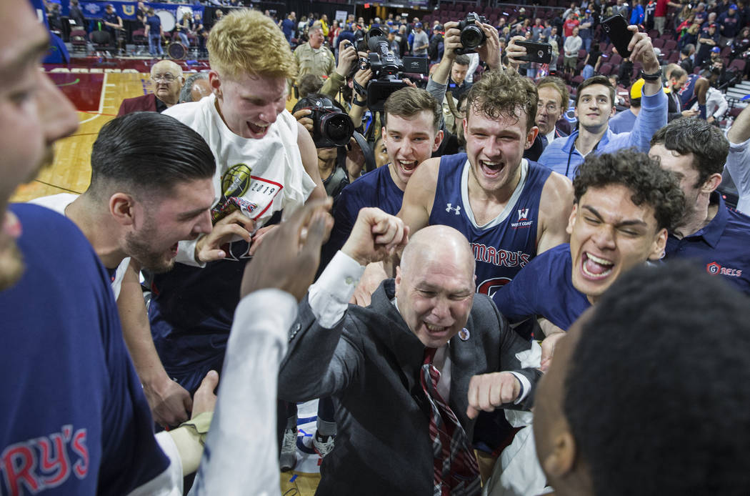 St. Mary's head coach Randy Bennett, middle, celebrates with his team after the Gaels upset Gonzaga 60-47 to win the West Coast Conference championship on Tuesday, March 12, 2019, at Orleans Arena ...