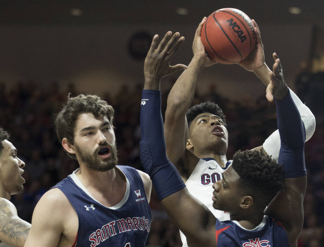 Gonzaga junior forward Rui Hachimura (21) grabs a rebound over St. Mary's sophomore forward Malik Fitts (24) and senior center Jordan Hunter (1) in the first half during the West Coast Conference ...