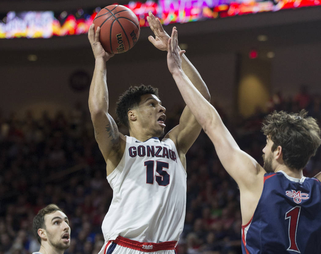 Gonzaga junior forward Brandon Clarke (15) drives past St. Mary's senior center Jordan Hunter (1) in the first half during the West Coast Conference finals game on Tuesday, March 12, 2019, at Orle ...