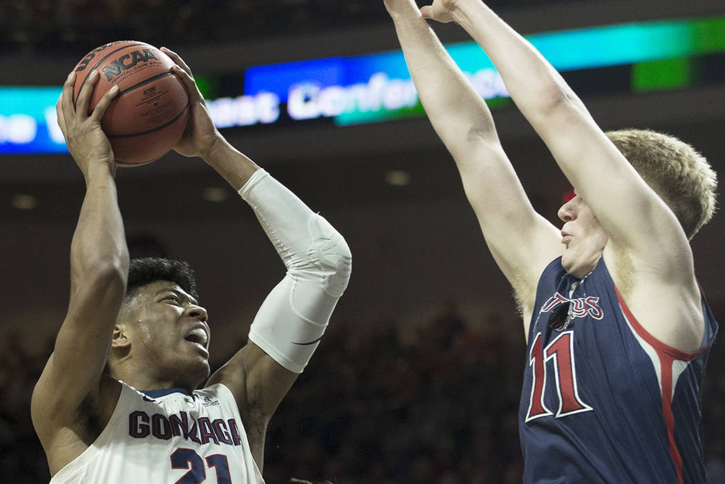 Gonzaga junior forward Rui Hachimura (21) drives over St. Mary's freshman forward Matthias Tass (11) in the first half during the West Coast Conference finals game on Tuesday, March 12, 2019, at O ...