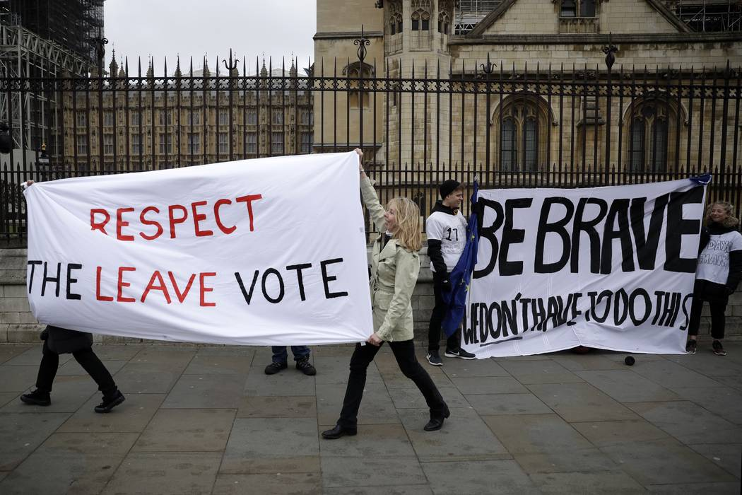 Pro-Brexit leave the European Union supporters, left, and anti-Brexit remain in the European Union supporters take part in a protest outside the Houses of Parliament in London, Tuesday, March 12, ...