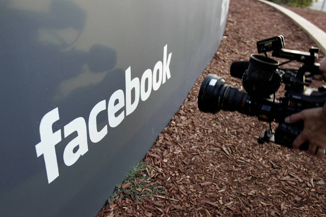 In this file photo a television photographer shoots the sign outside of Facebook headquarters in Menlo Park, Calif. (AP Photo/Paul Sakuma)
