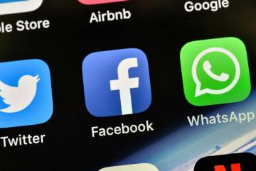 The icons of Facebook and WhatsApp are pictured on an iPhone. (AP Photo/Martin Meissner)