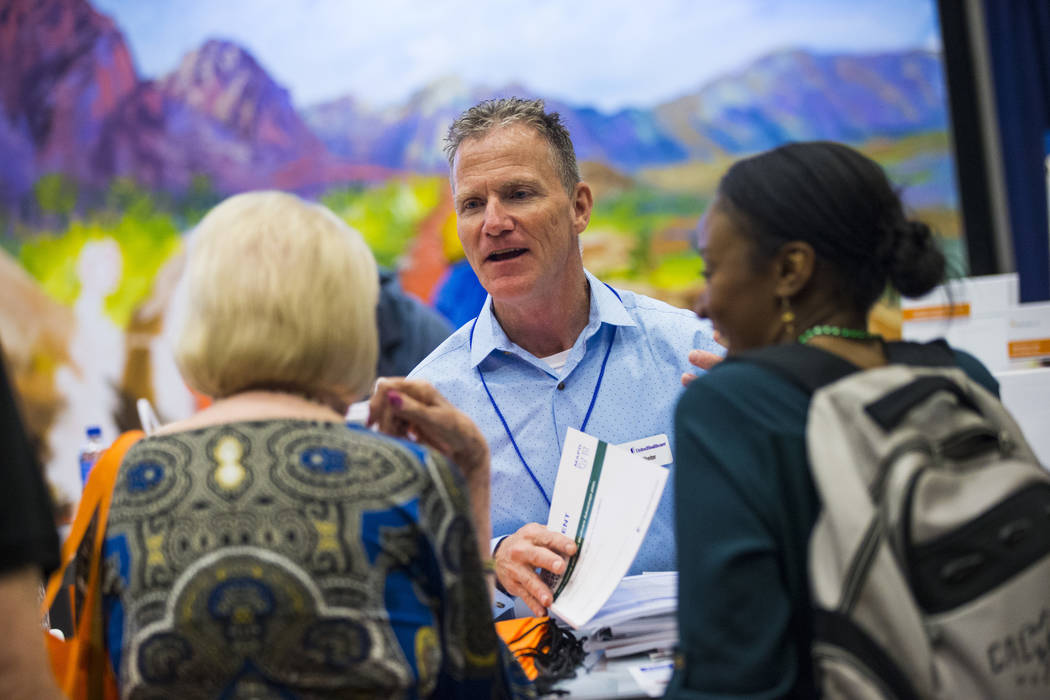 Daniel Hunter, a sales representative with UnitedHealthcare, talks with attendees during the fifth annual AgeWell Expo at the Rio Convention Center in Las Vegas on Saturday, March 16, 2019. (Chase ...