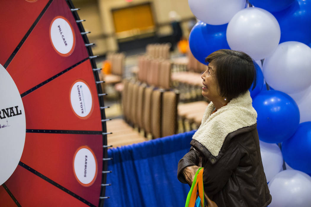 Lina Gozo of Henderson watches a wheel spin as part of a Review-Journal promotional giveaway during the fifth annual AgeWell Expo at the Rio Convention Center in Las Vegas on Saturday, March 16, 2 ...