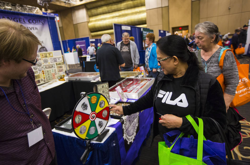 Catalina Perito of Las Vegas, right, spins a wheel for a giveaway as Christopher Shands of Archangel Coins looks on during the fifth annual AgeWell Expo at the Rio Convention Center in Las Vegas o ...
