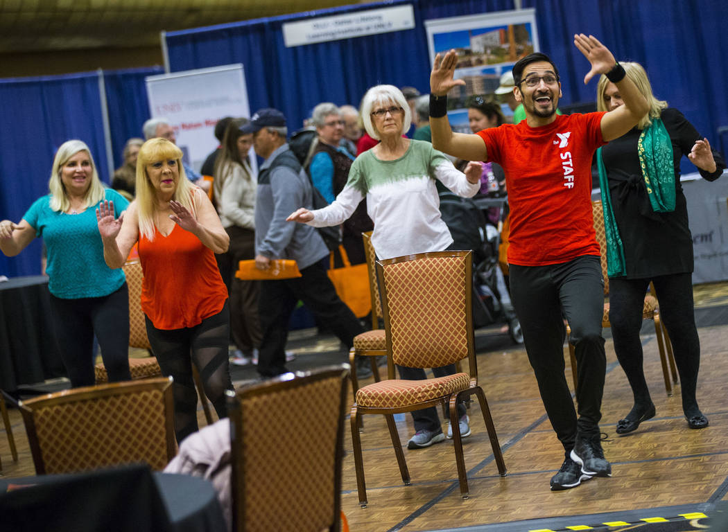 Jonathan Jimenez, health & wellness coordinator at the Bill & Lillie Heinrich YMCA, leads attendees in a Silver Sneakers exercise during the fifth annual AgeWell Expo at the Rio Convention ...
