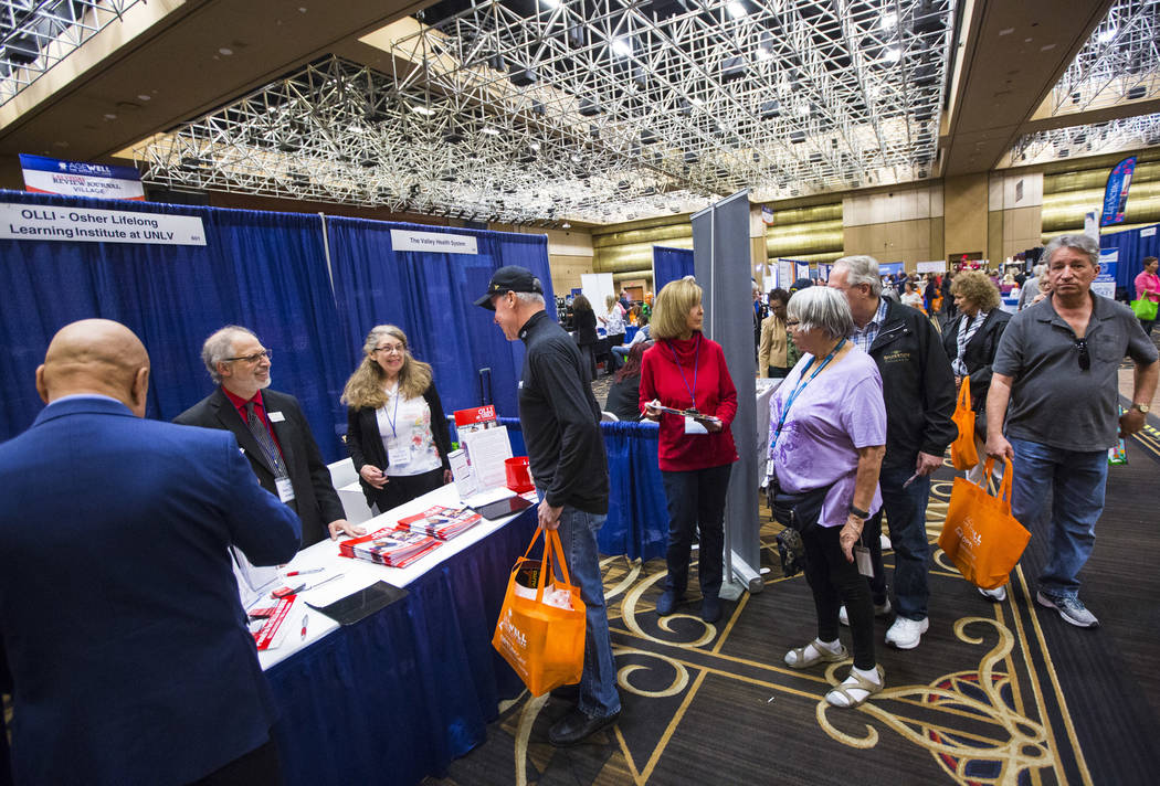Robert Levrant, far left, director of the Osher Lifelong Learning Institute, or OLLI, at UNLV, talks with attendees during the fifth annual AgeWell Expo at the Rio Convention Center in Las Vegas o ...