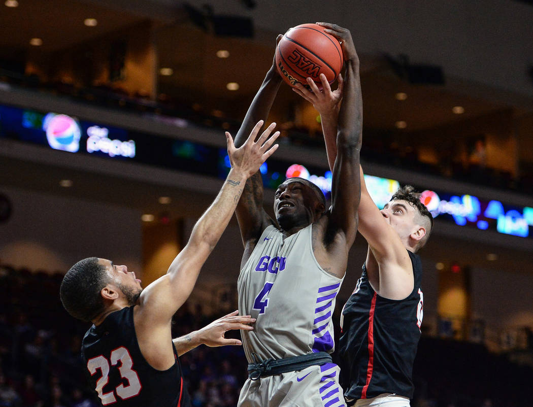 Grand Canyon forward Oscar Frayer (4) jumps up for a rebound while being guarded by Seattle guard Terrell Brown (23) and guard Rip Economou (11) in the first half of the opening round of the Weste ...
